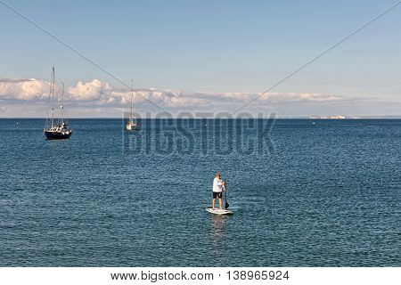 Swanage Dorset UK - July 2016. Eldery male paddles a paddleboard at the sea