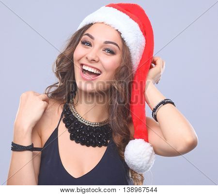 Attractive smiling woman in Santa Cap. Isolated over a gray background.
