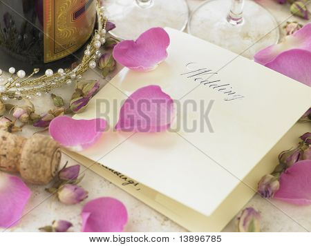 Invitación de la boda al lado de la botella de Champagne rodeado de pétalos de flores