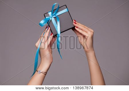 Girl's hands holding a beautiful black box for jewelry with blue bow