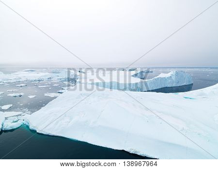 Icebergs are melting to arctic ocean, north pole in Greenland