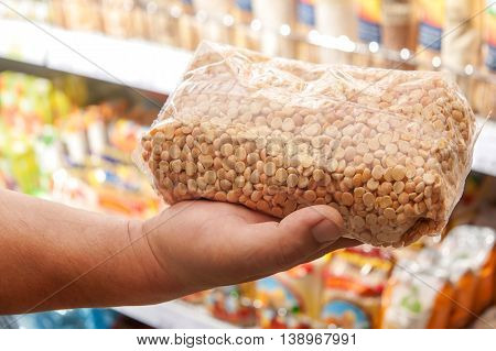 Packages with peas in the buyer's hand in the store