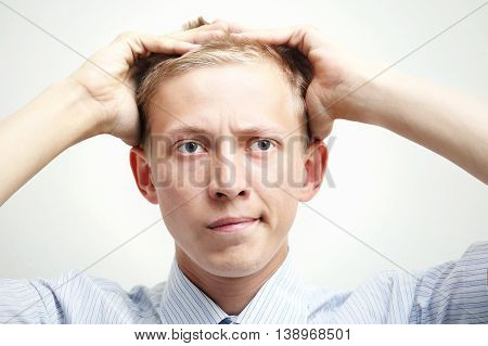 Young man grabbing his head and thinking about problem
