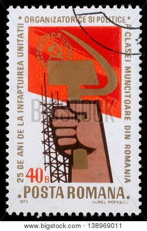 ROMANIA - CIRCA 1973: A stamp printed in Romania showing a hand holding sickle and hammer, circa 1973
