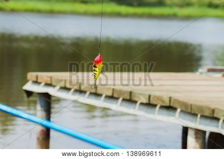 Fishing bright lure a predator spinning on natural background close-up - concept of a rural getaway and fishing