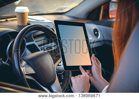 Young, beautiful woman driving a car with a tablet in hands. Back view. Safe driving concept. Multitasking