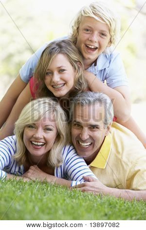 Family Lying On Top Of Each Other In A Park