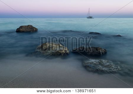 Beautiful misty beach at sunrise, sandy beach with rock formations, a distant sailboat on the horizon