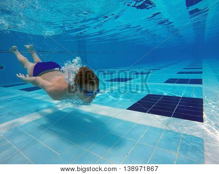 boy diving into a swimming pool