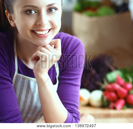 Young woman standing in her kitchen near desk .
