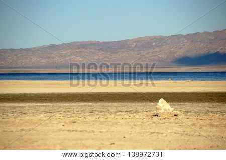 The shore of the Salton Sea with towering chunks of earth and salt deposits.
