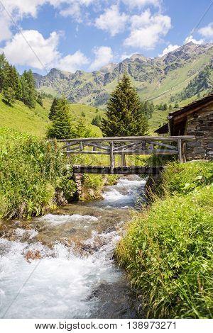 vertical mountain panorama with a wooden bridge on a creek - Ponte di Legno Italy