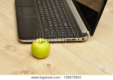 A green apple displayed next to a laptop