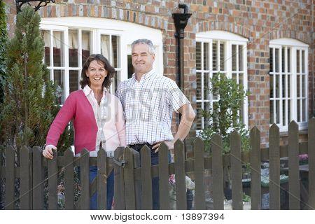 Granjero y esposa de pie delante de casa de campo