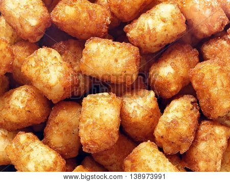 close up of rustic golden potato tater tots food background