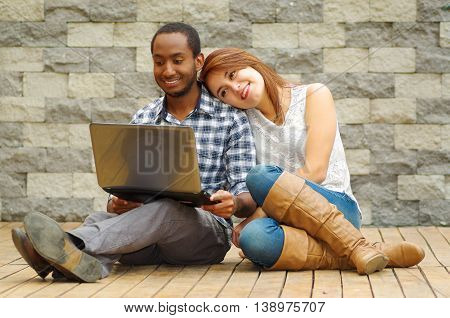 Interracial charming couple wearing casual clothes sitting down on wooden surface lookin at laptop together, in front of grey brick wall.