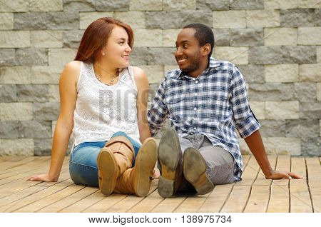 Interracial charming couple wearing casual clothes sitting on wooden surface posing for camera staring at each other, grey brick wall background.