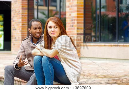 Interracial happy charming couple sitting on steps in front of building interacting and smiling for camera.