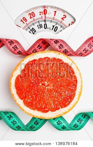 Dieting healthy eating slim down concept. Closeup grapefruit slice with measuring tape on white weight scale