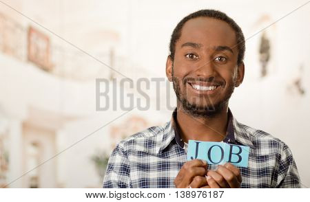 Headshot handsome man holding up small letters spelling the word job and smiling to camera.
