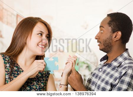 Interracial charming couple holding up large puzzle pieces and happily interacting having fun, blurry studio background.