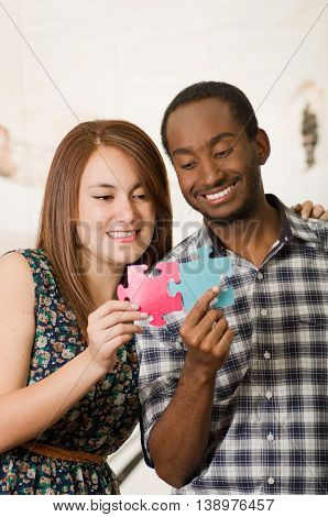 Interracial charming couple embracing friendly, holding up large puzzle pieces and happily interacting having fun, blurry studio background.