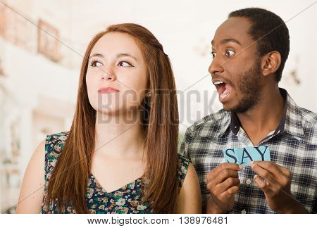 Charming interracial couple holding up small letters spelling the say while interacting happily, blurry studio background.
