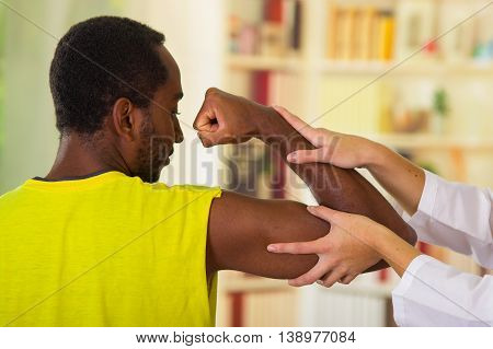 Man getting physical arm treatment from physio therapist, her hands working on his shoulder and elbow, medical concept.