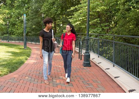 2 african american college women walking and talking on campus