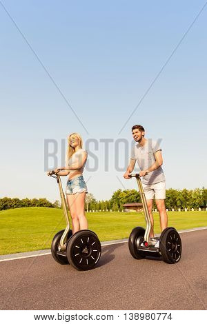 Young Happy Tourist Couple In Love Riding Segway