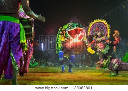 BAMNIA PURULIA WEST BENGAL INDIA - DECEMBER 23RD 2015 : Dancer dressed as Crocodile is acting as killing people Chhau Dance festival. It is a very popular Indian tribal martial dance performed at night amongst spectators.