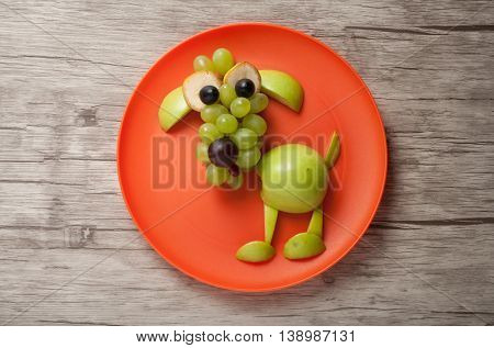 Funny dog made of fruits on plate and board