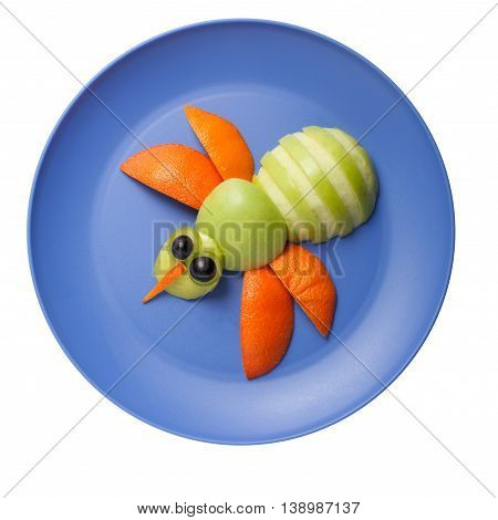Bee made of fresh fruits on blue plate