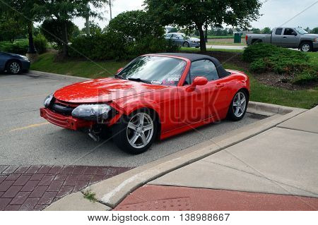 SHOREWOOD, ILLINOIS / UNITED STATES - AUGUST 30, 2015: A red automobile, missing its front bumper, sits parked in a parking lot in Shorewood, Illinois.