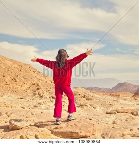 Young girl standing over beautiful mountain view. Freedom concept.