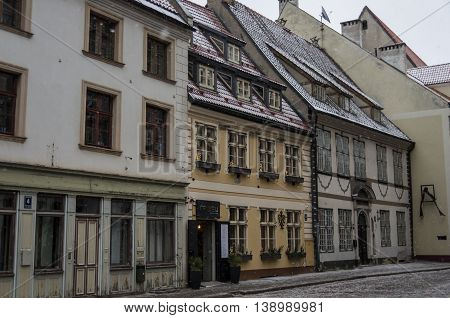 Riga, Latvia - January 1, 2016: Traditional medieval houses in street of Riga old town. Winter and snow.
