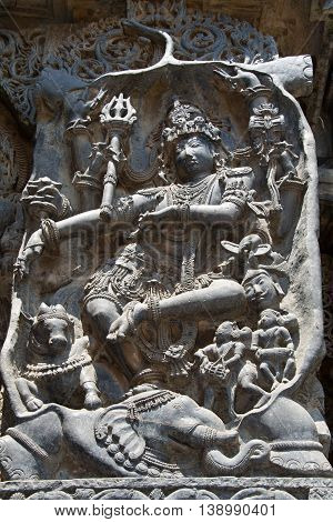 Shiva killing a demon Gajasura appearing in the guise of an elephant by dancing inside and piercing its skin; wall carving in Hoysaleshwara temple at Halebidu Hassan district Karnataka state India Asia