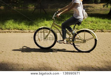 Motion blur. Young girl riding on bicycle in the park by road at summertime
