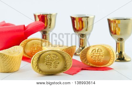 Gold ingot Red ribbon bow Gold jug Tea glass on white background.