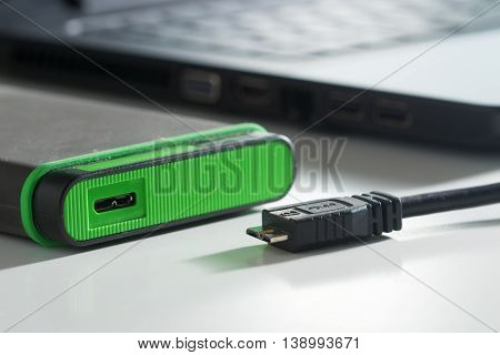 Green external hard disk with cable on white