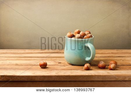 Hazelnuts in cup on wooden table over grunge background