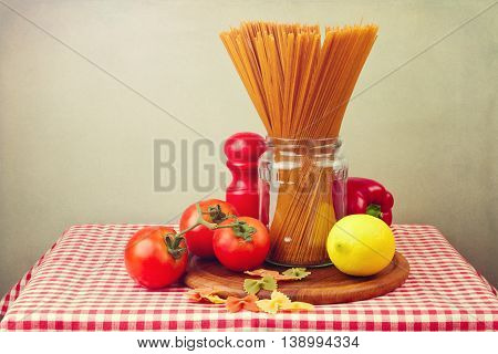 Whole wheat spaghetti and vegetables on red tablecloth. Still life composition.