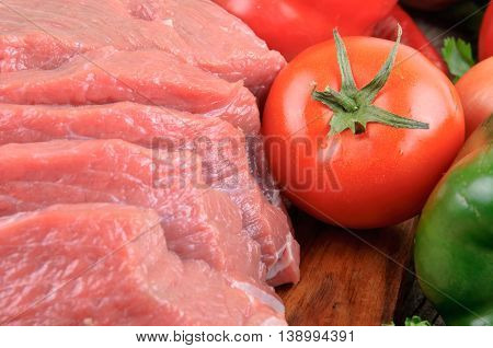Juicy slices of meat with vegetables on wooden board close up. Food background
