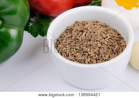 Cumin seeds in white bowl with vegetables on a white background. Food background