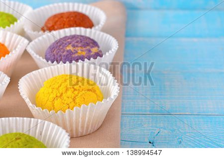 Set of different cake shu eclairs on a blue wooden table with copy space