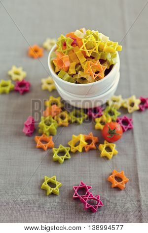 Colorful star shape pasta on textile background