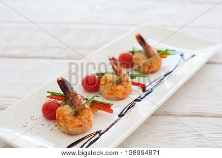 Plate of grilled shrimps with vegetables on white wooden background. Blurred background, free space for text