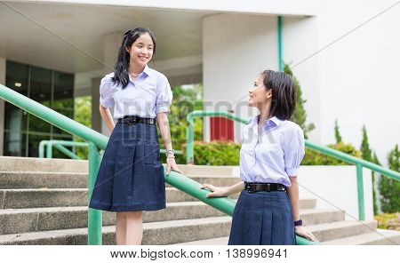 Cute Asian Thai high schoolgirls student couple in school uniform sit on the stairway chatting with a happy smiling face together on a building stairs