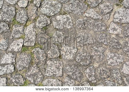 Gray old stone pavement pattern in a sunny day.