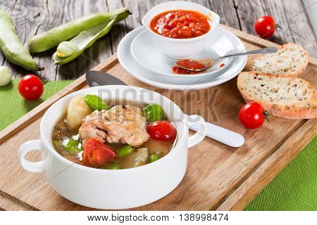 Braised chicken things with new potatoes tomatoes and butter lima bean in graten dish and in soup bowl on table mat tomato and bell pepper sauce in gravy boat view from above